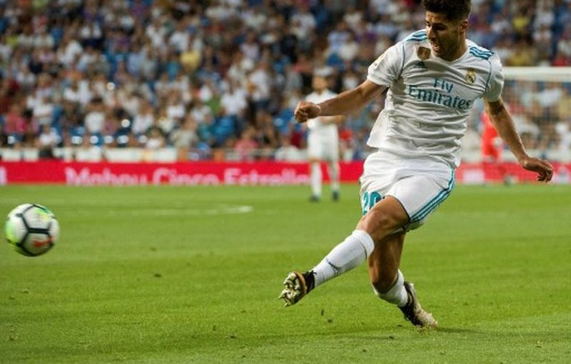 Real Madrid's midfielder Marco Asensio kicks the ball during the Spanish league football match Real Madrid CF vs Valencia CF at the Santiago Bernabeu stadium in Madrid on August 27, 2017. The game ended with a draw 2-2. / AFP PHOTO / CURTO DE LA TORRE